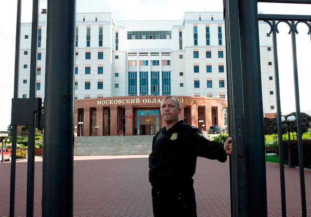 A bailiff outside the Moscow regional court building, where three people being taken to trial for robbery and murder were shot dead after they grabbed guns in an attempt to escape. Photo: Reuters