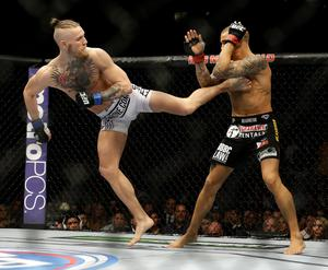 Connor McGregor kicks Dustin Poirier in their featherweight mixed martial arts bout at UFC 178 on Saturday, Sept. 27, 2014, in Las Vegas. (AP Photo/John Locher)