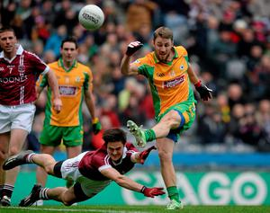 Micheal Lundy shoots to score Corofin's first point despite the challenge of Slaughtneil's Christopher McKaigue