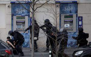 A suspect in a hostage taking situation is detained by members of special French RAID forces outside the post offices in Colombes outside Paris, January 16, 2015.  REUTERS/Philippe Wojazer