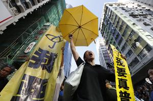 A pro-democracy protester chants umbrella and a yellow banner at an occupied area before the barricade is removed in Mong Kok district of Hong Kong Tuesday, Nov. 25, 2014.  (AP Photo/Kin Cheung)