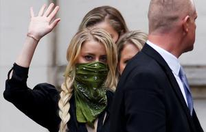 Turbulent relationship: Actor Amber Heard waves to onlookers as she leaves the High Court in London yesterday. Photo: REUTERS/John Sibley