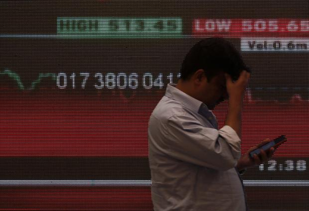 A man stands in front of a screen displaying news of markets update inside the Bombay Stock Exchange (BSE) building in Mumbai. Photo: Reuters