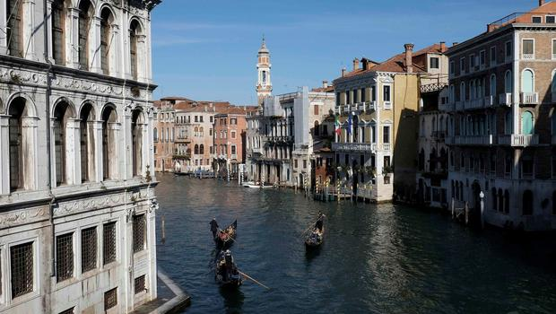 Gondoliers row in Gran Canal in Venice. The sleek black gondolas that whisper through Venice bear the hallmarks of a tiny but proud group of artisans striving to keep alive the traditional building methods for the floating city's most recognizable symbol