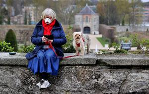 Braving the outdoors: Pauline Goodwin, wearing a face mask, and her dog Pixie Buttons pause for a moment in the sunshine at the Royal Hospital Kilmainham in Dublin. Photo: Steve Humphreys