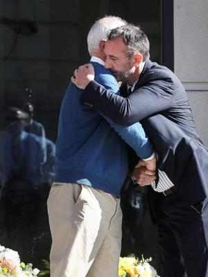 Berkeley Mayor Tom Bates (L) hugs Philip Grant, Consul General of Ireland to the Western United States, following a wreath-laying ceremony at the scene of a 4th-story apartment building balcony collapse in Berkeley, California June 16, 2015. REUTERS/Elijah Nouvelage