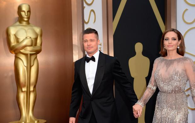 Actors Brad Pitt and Angelina Jolie arrive on the red carpet for the 86th Academy Awards on March 2nd, 2014 in Hollywood, California. AFP PHOTO / Robyn BECK        (Photo credit should read ROBYN BECK/AFP/Getty Images)
