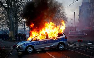 A German police car that was set on fire by anti-capitalist protesters burns outside the European Central Bank (ECB) headquarters hours before the official opening of its new building in Frankfurt