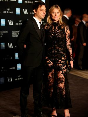Model Kate Moss, right, and her husband Jamie Hince pose for photographers upon arrival at the Alexander McQueen Savage Beauty Gala exhibition