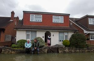 Nikki Vipers (left) with her dad Andy and mum Sharon (right) looks at their flooded garden in Egham, Surrey. Steve Parsons/PA Wire