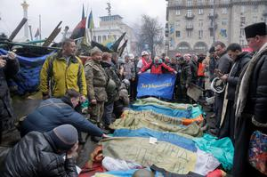 """Activists and priests pay respects to protesters who were killed in clashes with police, a flag held by one activist reads """"For Ukraine."""" in Kiev's Independence Square."""