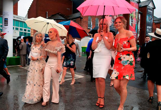 Female racegoers shelter from the rain during Ladies Day of the 2018 Randox Health Grand National Festival at Aintree Racecourse, Liverpool