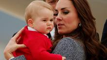 Kate Middleton holds her son Prince George with Australian Prime Minister Tony Abbott behind them, as they prepare to board a plane with her husband Prince William to depart Canberra