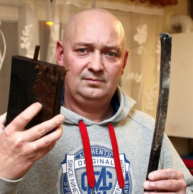 Robert Mielnik pictured with a block of wood and a steel bar which were thrown at his Clondalkin home