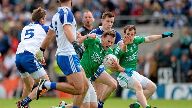 Declan McCusker goes down under pressure from Monaghan's Dessie Mone, left, and Owen Duffy