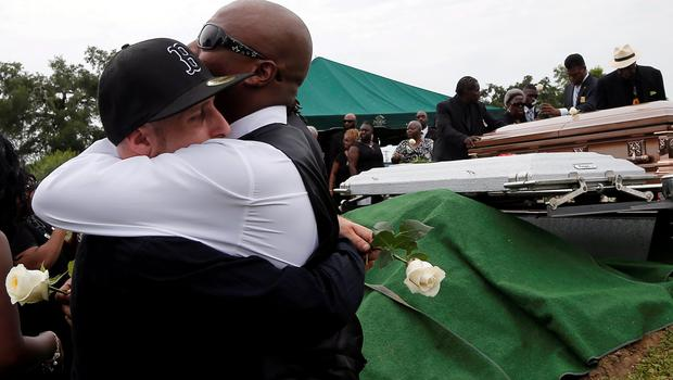 Mourners hug as Ethel Lance is buried at the Emanuel African Methodist Episcopal Church cemetery in North Charleston, South Carolina. Lance was one of the nine victims of the shooting at the Emanuel African Methodist Episcopal Church. Photo: Reuters/Brian Snyder