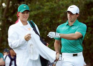 Tennis player Caroline Wozniacki of Denmark (L) works as the caddie for her ex, Northern Ireland's Rory McIlroy, during last year's Masters