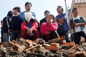 In this April 27, 2015 photo, locals watch rescue teams try to remove the body of a 12-year-old girl from a collapsed home in Kathmandu, Nepal. A strong earthquake shook Nepal's capital and the densely populated Kathmandu Valley on Saturday. (AP Photo/Wally Santana)