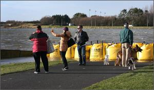 Walkers survey the damage at Clontarf car park at high tide today. Picture: Steve Humphreys