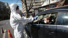 A Turkish health official wearing a protective face mask and suit as a preventive measure against the spread of the coronavirus, measures the temperature of a driver at a checkpoint in Ankara. AP Photo/Burthan Ozbilici