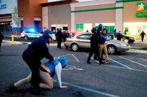 """Baltimore police officers tackle and arrest looters after they emerged from a """"Deals"""" store with merchandise during clashes between rioters and police in Baltimore, Maryland. Photo: Reuters"""