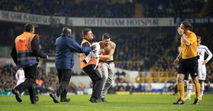 A second pitch invader is grabbed by security during the UEFA Europa League match at White Hart Lane