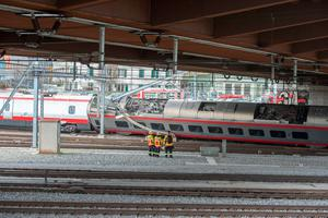 Rescuers stand next to a derailed train in the train station of Lucerne, Switzerland   (Urs Flueeler/Keystone via AP)