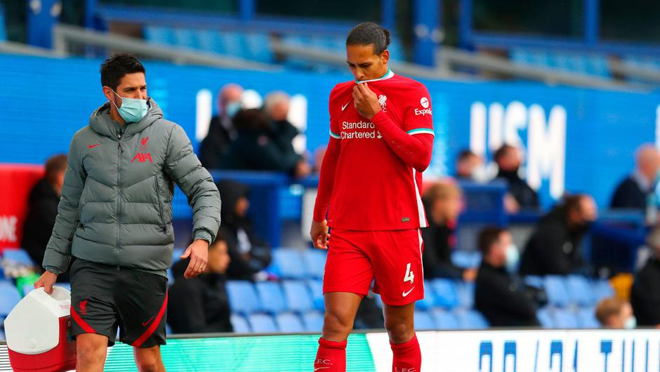 Van Dijk leaves the pitch with a member of Liverpool's medical team. Photo: Catherine Ivill/Getty Images