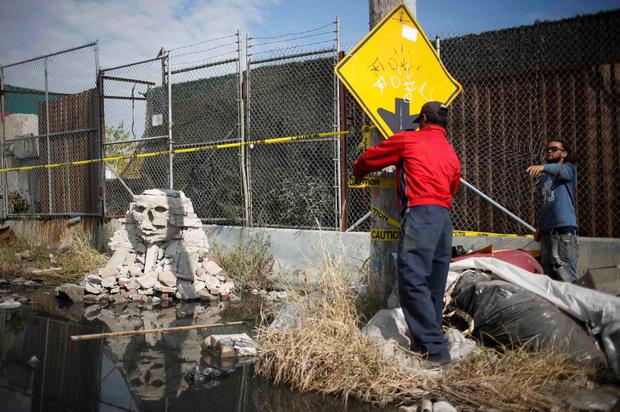 Men secure a rock formation by British graffiti artist Banksy with police tape in the Queens borough of New York