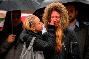 Two women comfort each other during a minute's silence on London Bridge in honour of the terror attack victims. Photo: PA