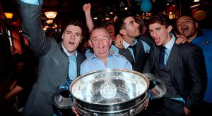 Pub owner Hugh Hourican with Dublin Footballers Paddy Andrews, left, Michael Darragh MacAuley, and Michael Fitzsimons, right, with the Sam Maguire Cup, celebrating the morning after their All-Ireland victory over Kerry. Boar's Head, Capel Street, Dublin. Picture: Caroline Quinn
