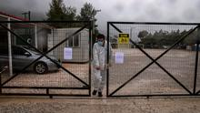 A man wearing a protective suit and a face mask exits the Malakasa migrant camp after authorities found a coronavirus case and placed the camp under quarantine. Photo: REUTERS/Alkis Konstantinidis