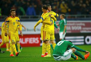 Romania's Vlad Chiriches (centre R) hugs his teammate Dragos Grigore as Mihai Pintilii (L) looks on after their Euro 2016 Group F qualifying soccer match against Northern Ireland at National Arena in Bucharest