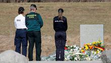 Spanish police officers pay tribute next to a stele and flowers laid in memory of the victims in the area where the Germanwings jetliner crashed in Le Vernet, France (AP Photo/Claude Paris)
