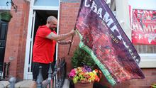 A Liverpool fan puts a flag outside his home after the club ended their 30-year wait for the League title