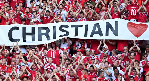 Denmark fans react after the ball is kicked out in the 10th minute of the match to applaud Denmark's Christian Eriksen who remains in hospital after collapsing during the match between Denmark and Finland last Saturday. REUTERS/Stuart Franklin