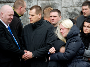 Neighbour Kevin Hennessey commiserates with parents Vidas and Aukse with daughter Agnita pictured at the funeral of Vakaris Martinaitis at the Church Of The Most Holy Rosary, Midleton.