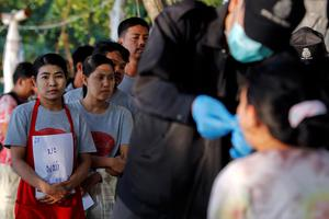 People wait in line as policemen collect data from those who work near the spot where bodies of two killed British tourists were found, on the island of Koh Tao. Photo credit: REUTERS/Chaiwat Subprasom