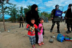 A migrants woman with childrens wait to pass the Greek-Macedonian border, guarded by Macedonian police near the town of Idomeni, northern Greece, on August 21, 2015. Macedonian police have reinforced control at the border with Greece in a bid to stop the influx of migrants, but a few hundred Syrians managed to cross the frontier overnight into August 21. Police prevented reporters to access a no-man's land where on August 20, officers had been in a standoff with about 1,500 migrants and refugees who wanted to cross into Macedonia. AFP PHOTO /SAKIS MITROLIDISSAKIS MITROLIDIS/AFP/Getty Images