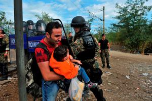 A migrant with a child attempts to pass the Greek-Macedonian border, guarded by Macedonian police near the town of Idomeni, northern Greece, on August 21, 2015. Macedonian police have reinforced control at the border with Greece in a bid to stop the influx of migrants, but a few hundred Syrians managed to cross the frontier overnight into August 21. Police prevented reporters to access a no-man's land where on August 20, officers had been in a standoff with about 1,500 migrants and refugees who wanted to cross into Macedonia. AFP PHOTO /SAKIS MITROLIDISSAKIS MITROLIDIS/AFP/Getty Images