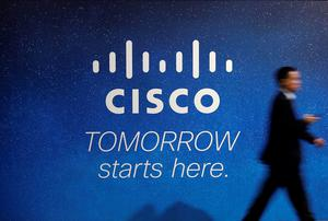 A visitor walks past a Cisco advertising panel at the Mobile World Congress in Barcelona earlier this year
