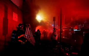 Baltimore firefighters rush ladders into position to fight fires in mutliple burning buildings set ablaze by rioters in Baltimore, Maryland. Photo: Reuters