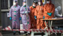 Medical professionals, in protective gear, look at decontamination trucks arriving at the preliminary testing facility against the coronavirus (COVID-19) in the Eunpyeong district on March 04, 2020 in Seoul, South Korea.  (Photo by Woohae Cho/Getty Images)