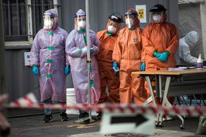 Medical professionals, in protective gear, look at decontaminationtrucks arriving at the preliminary testing facility against the coronavirus (COVID-19) in the Eunpyeong district on March 04, 2020 in Seoul, South Korea.  (Photo by Woohae Cho/Getty Images)