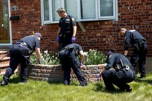 NYPD officers search for the weapon used to shoot New York City plainclothes police officer Brian Moore at the Queens Village, in New York May 3, 2015. REUTERS/Eduardo Munoz