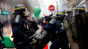 French riot police grab a protester during a rail workers' march in Paris last week. Photo: Christophe Ena