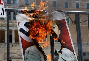 A poster depicting German Chancellor Angela Merkel wearing a Nazi uniform is set on fire by a protester in front of the parliament in Athens' Syntagma square