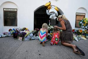 Mourners kneel outside the Emanuel African Methodist Episcopal Church in Charleston, South Carolina June 18, 2015 a day after a mass shooting left nine dead during a bible study at the church