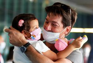 Hug: A man is reunited with his daughter at Rome airport as she comes back with his wife from Colombia after Italy reopened its borders this week. Photo: Reuters