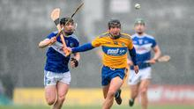Clare's David Reidy tries to keep James Keyes of Laois at bay during their Division 1, Group B match at Cusack Park in Ennis. Photo: Eóin Noonan/Sportsfile